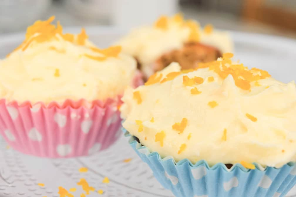 close up of 3 cupcakes, decorated with orange zest and in pink and blue cases