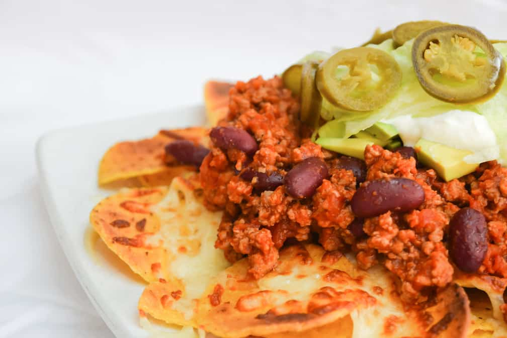 Close up photo of Chilli con carne atop of nachos with jalapeños and avocado