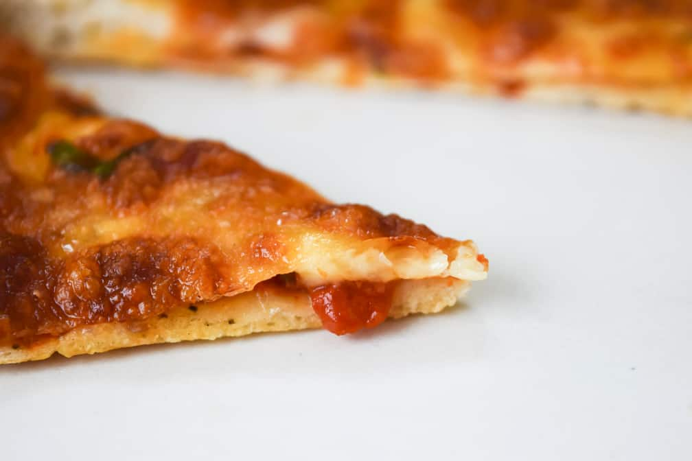slice of pizza with sauce spilling over the edge