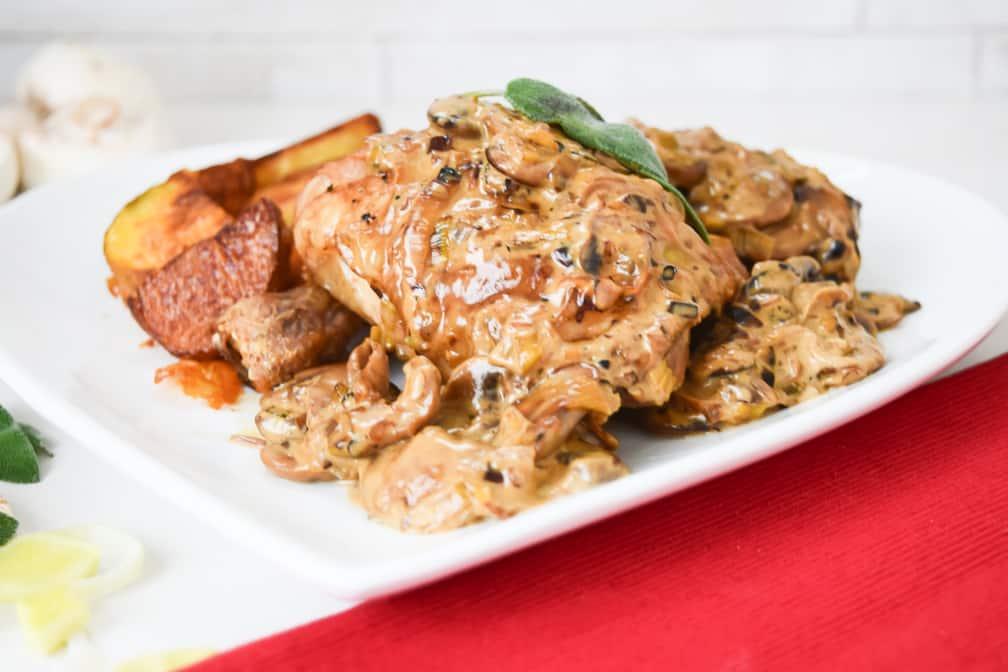 Butter sage chicken on a plate covered in mushroom sauce