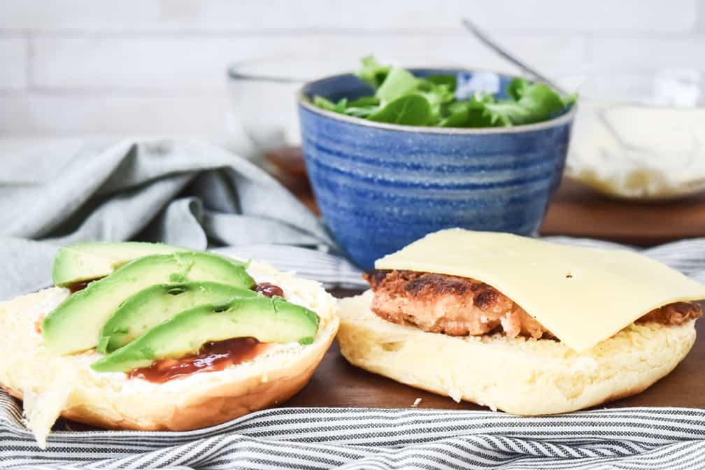 open burger with avocado and chicken inside