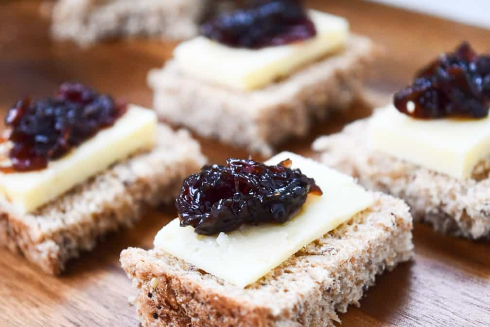 close up of onion chutney on top of cheese and sliced bread