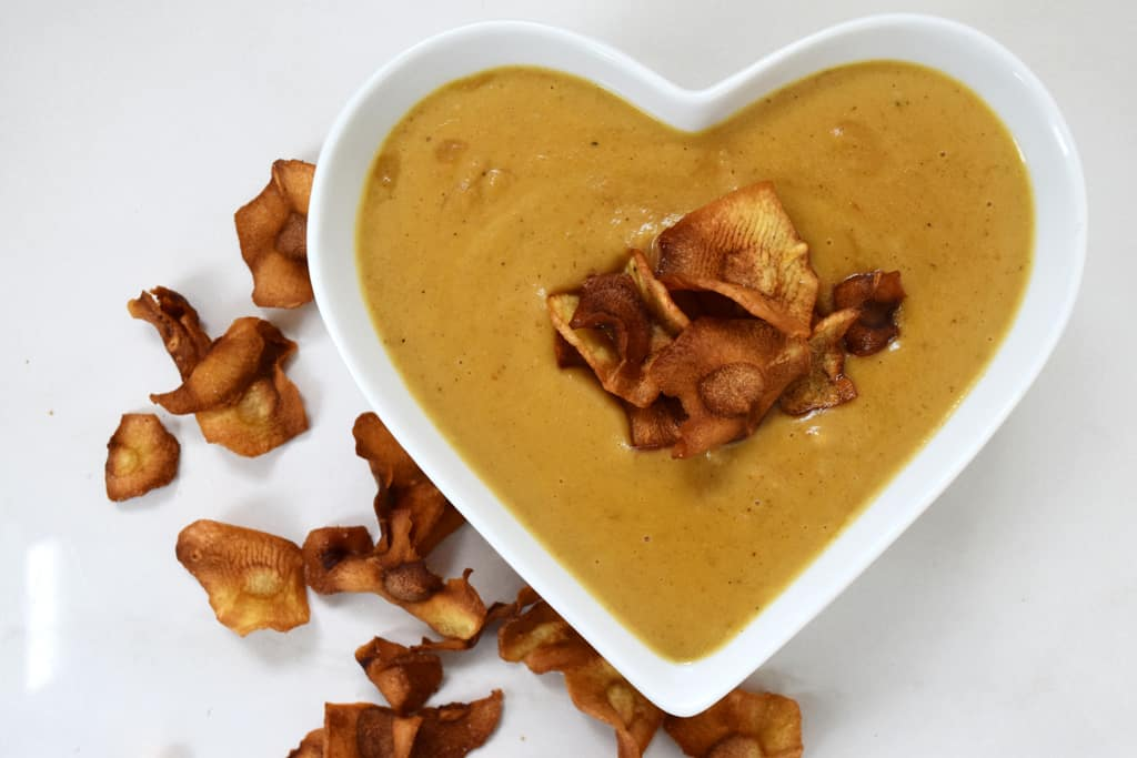 parsnip soup overhead view in a heart shaped bowl, decorated with parsnip crisps