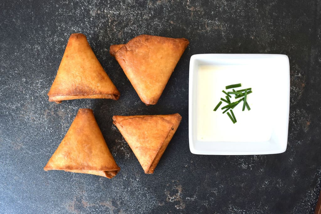 overhead view of four falafel samosas next to a white dipping sauce