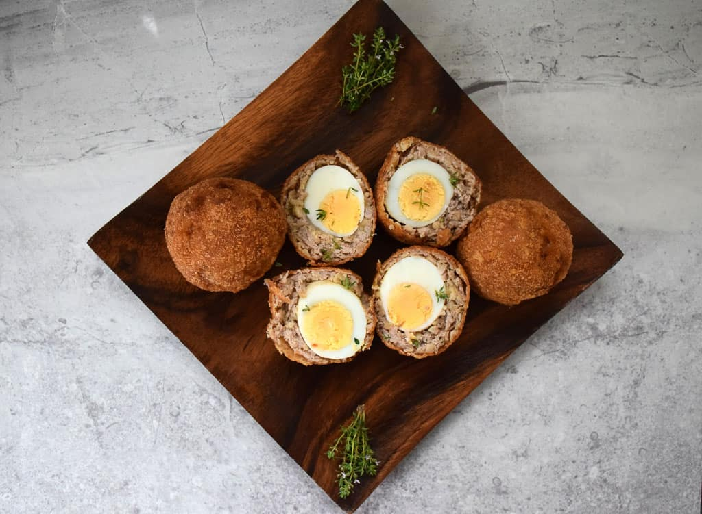 overhead view of scotch eggs, with two of them cut in half to show the inside
